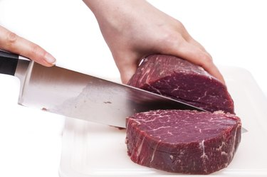 Cooking knife is slicing a fillet of beef
