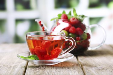 Fruit red tea with wild berries in cup, on table