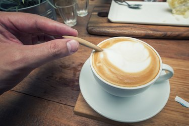 Close up hand mixing with a spoon of coffee.