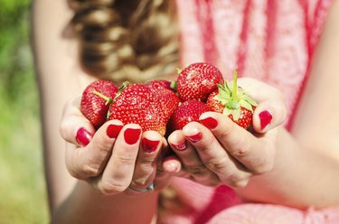 Hands of woman holding fresh strawberries