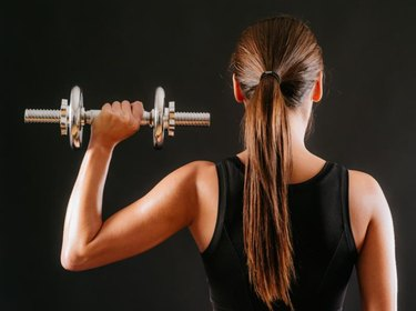 Photo of the back of a young woman doing a shoulder press with a dumbbell over a dark background.