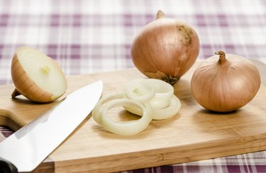 Onions and onion rings on cutting board with knife.