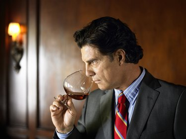 Mature man sniffing brandy from snifter