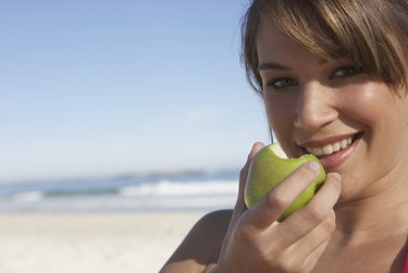 Young woman holding apple, outdoors, smiling, close-up, portrait