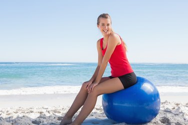 Athletic young woman sitting on exercise ball looking at camera