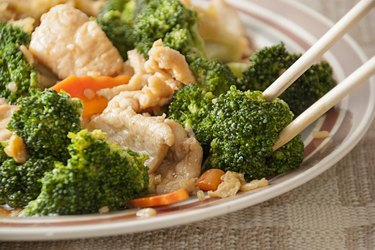 Closeup of an individual serving of chicken and broccoli, with very selective focus on the broccoli floret that is being held by the chopstick