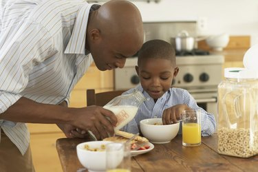 Father pouring milk in bowl for son (5-7) at breakfast table