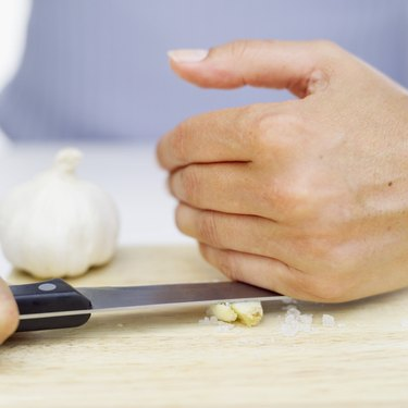 Person's hands crushing garlic with a knife