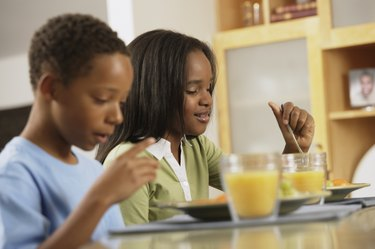 African brother and sister eating breakfast
