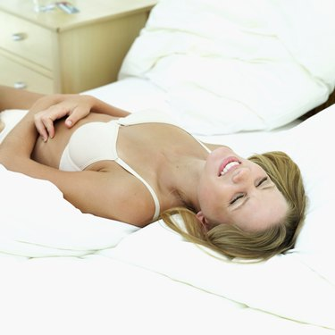 Elevated view of a young woman lying in bed and smiling