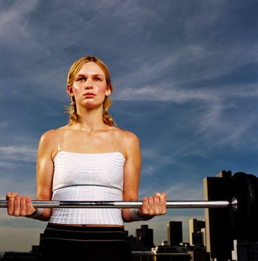 Portrait of a young woman carrying a barbell