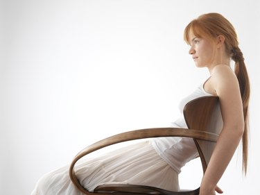 Young woman leaning back in chair, side view