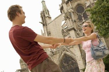 France, Paris, Notre-Dame, couple holding hands, smiling