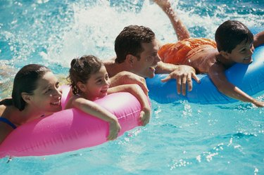 Family relaxing on inflatable rafts in a swimming pool