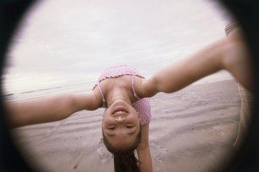 Girl bending over backwards on the beach
