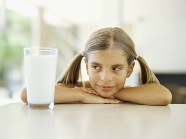Close-up of a girl looking at a  glass of milk
