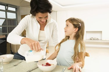 Close-up of a young woman serving breakfast to her daughter