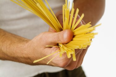 Close-up of uncooked spaghetti in a man's hands