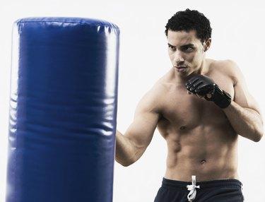 Mixed Race man using punching bag