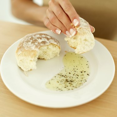 Close-up of a woman's hand holding a bap on a plate