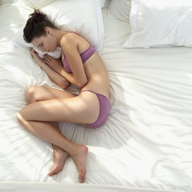 Elevated view of a young woman sleeping on a bed wearing her lingerie
