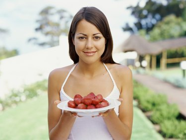 Portrait of a young woman holding a plate of strawberries