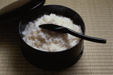 Cooked rice in bowl with scoop, high angle view