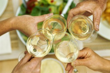 Elevated view of four glasses of white wine held together