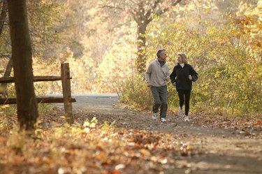 Couple jogging down path through fall leaves