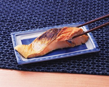 Chopsticks holding a piece of broiled sliced salmon on plate, high angle view