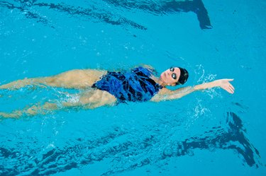 Woman swimming backstroke in pool