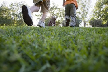 a group of young boys walking across grass