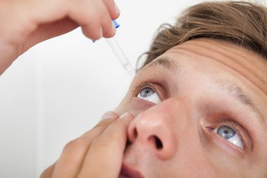 Young Man Putting Eye Drops In His Eyes