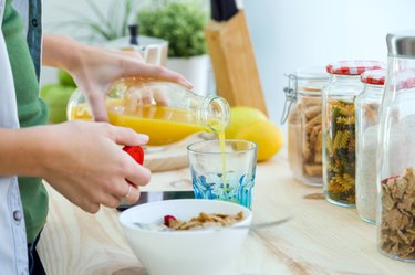 Hands showing woman enjoying breakfast in the kitchen.