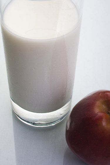 Glass of milk with an apple, studio shot
