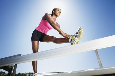 Athletic woman jumping over hurdle
