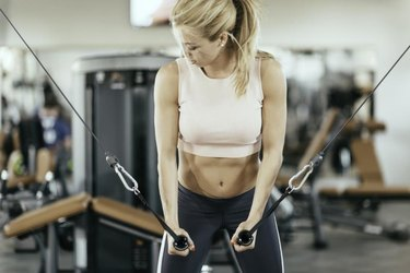 Female athlete exercising on cable crossover fitness machine in the gym