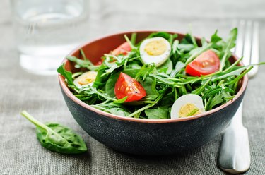 salad with arugula, spinach, tomatoes and eggs.
