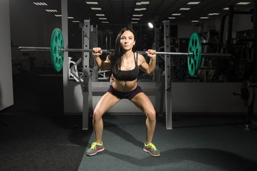 Brunette strong fitness sexy woman doing barbell squats in a