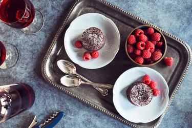 Two Baked Chocolate Lava Cakes with Raspberries and Red Wine