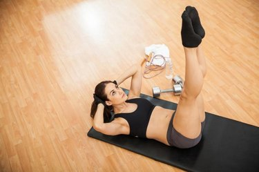Top view of a young woman keeping her legs raised and doing crunches at the gym