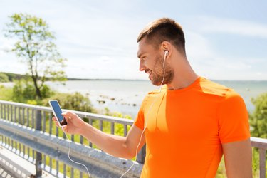 smiling young man with smartphone and earphones