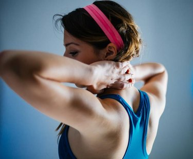 Fit woman showing how to perform a back straightening exercise