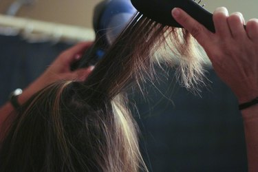 Woman Blow Drying Hair - Stock Image