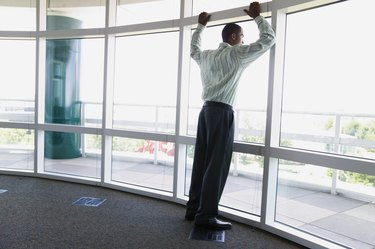 Rear view of a businessman leaning against a window frame