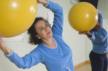 Senior Woman Using Exercise Ball in Fitness Class