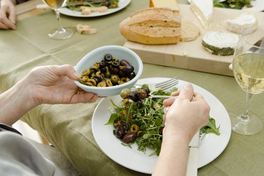 Woman adding olives to salad