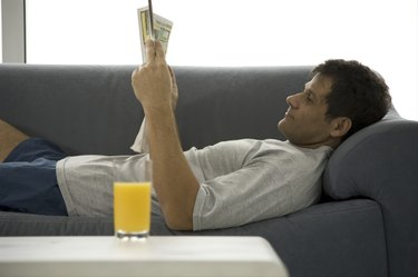 Mature man lying on couch and reading newspaper