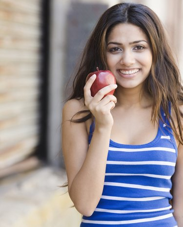 Middle Eastern woman holding apple