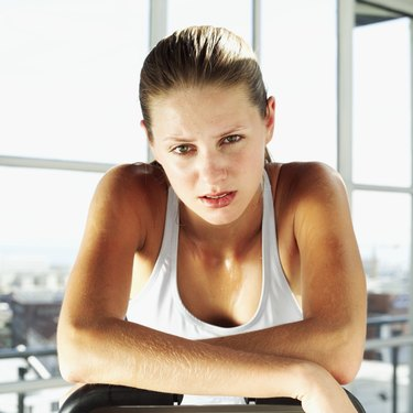portrait of a young woman leaning on an exercise bike
